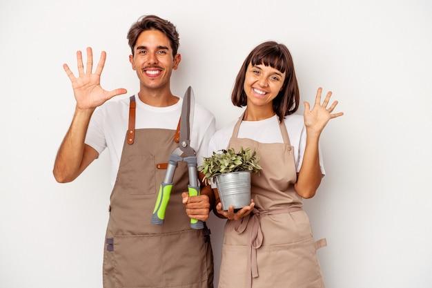 Jeune couple de jardinier métis isolé sur fond blanc souriant joyeux montrant le numéro cinq avec les doigts.