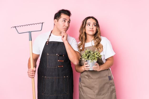 Jeune couple jardinier regardant de côté avec une expression douteuse et sceptique.