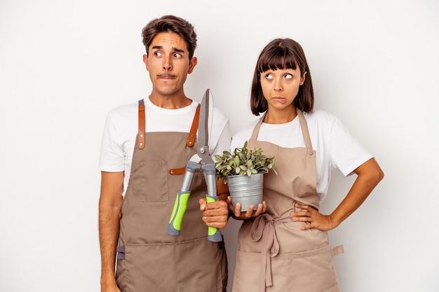 Jeune couple de jardiniers métis isolé sur fond blanc confus, se sent dubitatif et incertain.