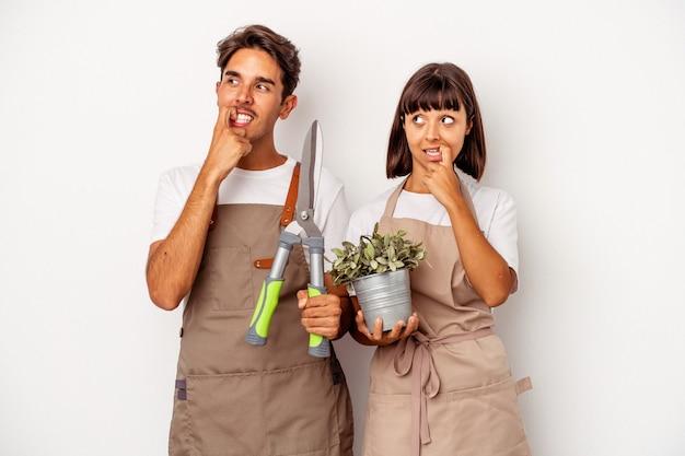 Jeune couple de jardiniers métis isolé sur fond blanc détendu en pensant à quelque chose en regardant un espace de copie.