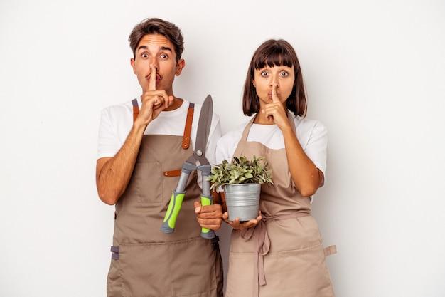 Jeune couple de jardiniers métis isolé sur fond blanc gardant un secret ou demandant le silence.