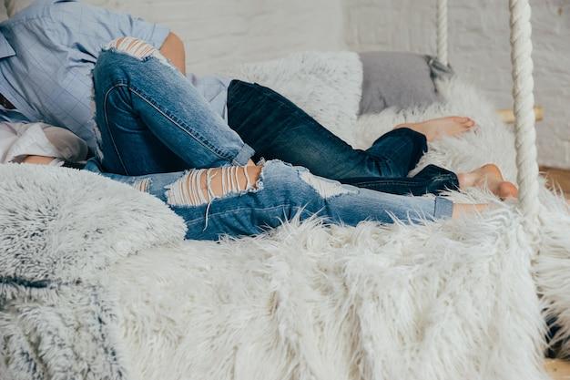 Un jeune couple en jeans sur un lit