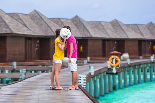 Jeune couple sur la jetée de la plage près d'une villa sur l'eau en lune de miel