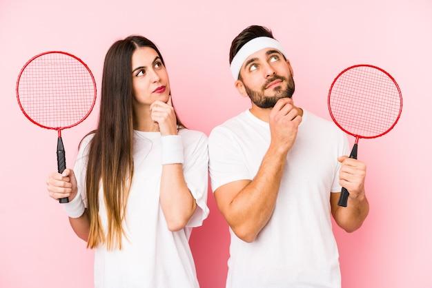 Jeune couple jouant au badminton à côté avec une expression douteuse et sceptique.