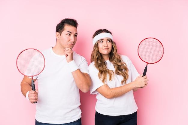 Jeune couple jouant au badminton isolé à côté avec une expression douteuse et sceptique.