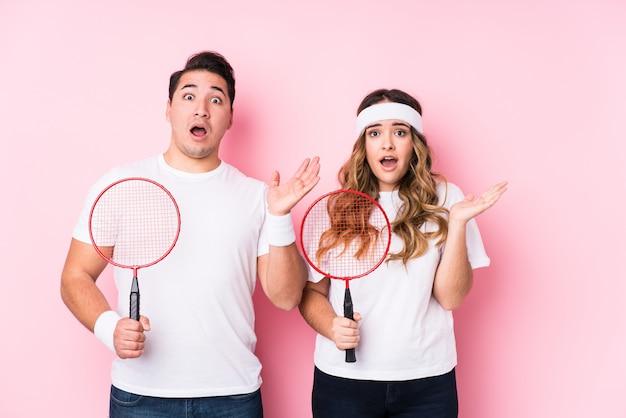 Jeune couple jouant au badminton isolé surpris et choqué.