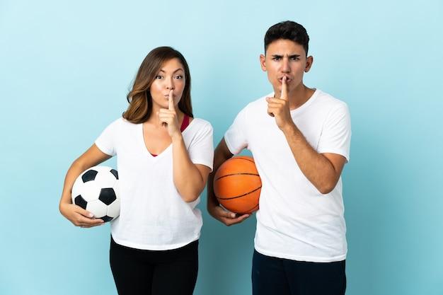 Jeune couple jouant au football et au basket-ball sur bleu montrant un signe de silence geste mettant le doigt dans la bouche