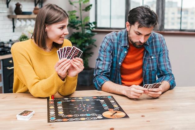 Jeune couple jouant au plateau de jeu sur un bureau en bois