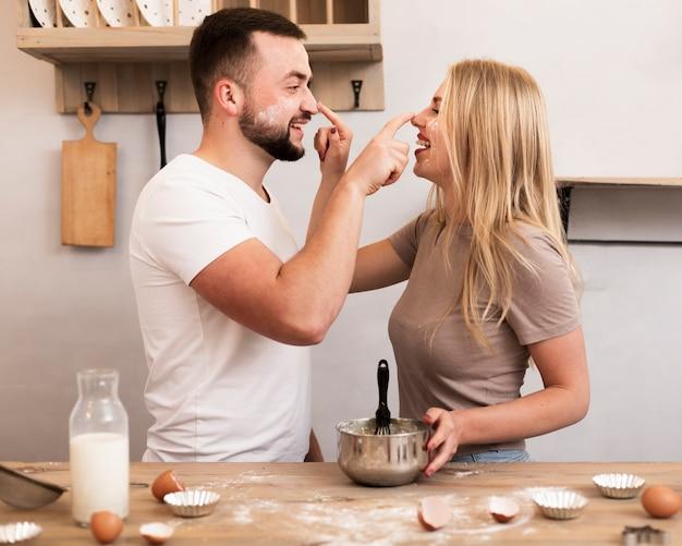 Jeune couple jouant avec de la farine dans la cuisine