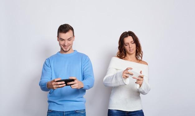 Jeune couple jouant à des jeux vidéo avec des téléphones portables.