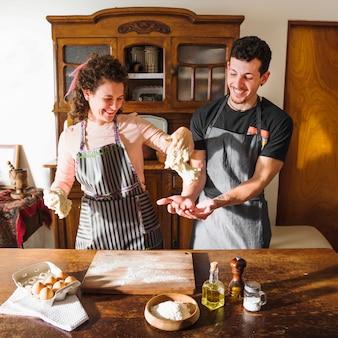 Jeune couple jouant avec de la pâte pétrie à la maison