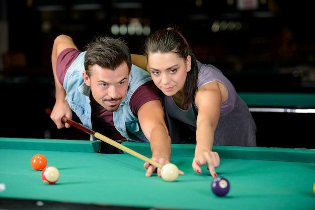 Jeune couple joue au billard dans le club de billard sombre