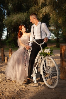 Jeune couple le jour du mariage avec un vélo