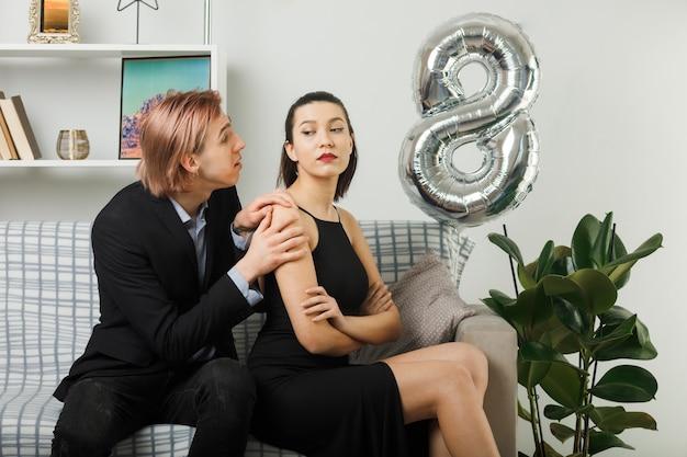Jeune couple le jour de la femme heureuse mec triste mettant les mains sur l'épaule d'une femme stricte assise sur un canapé dans le salon