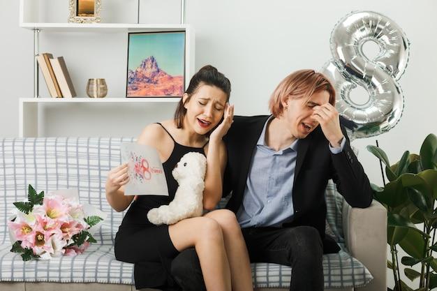 Jeune couple le jour de la femme heureuse avec ours en peluche et carte postale assis sur un canapé dans le salon
