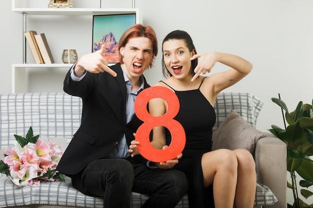 Jeune couple le jour de la femme heureuse tenant le numéro huit montrant le geste assis sur un canapé dans le salon