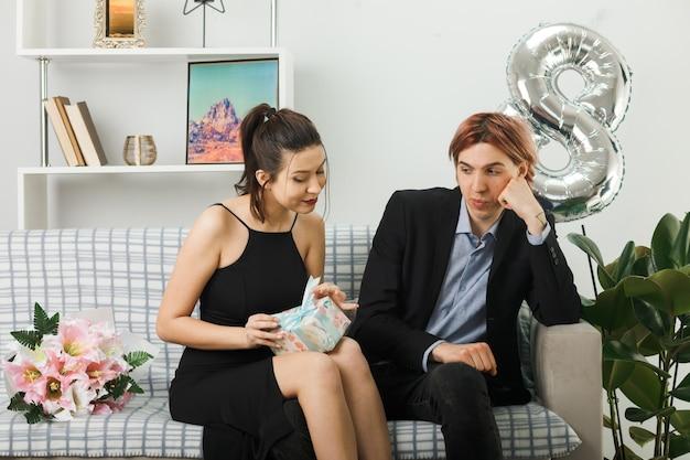 Jeune couple le jour de la femme heureuse tenant et regardant le présent assis sur un canapé dans le salon