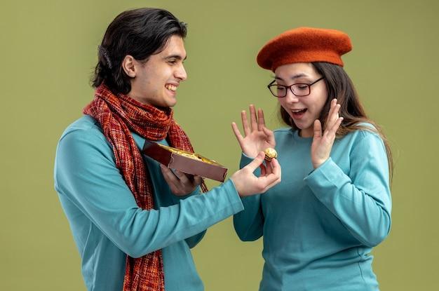 Jeune couple le jour de la saint-valentin gars portant une écharpe fille portant un chapeau mec souriant donnant boîte de bonbons isolé sur fond vert olive