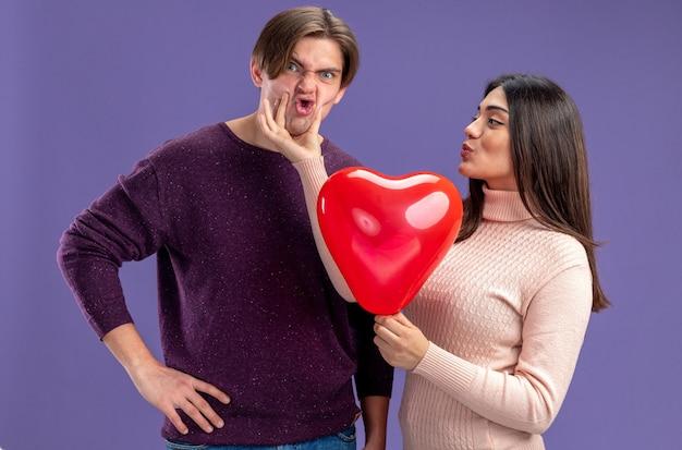 Jeune couple le jour de la saint-valentin heureux girl holding heart balloon attrapé guy menton isolé sur fond bleu