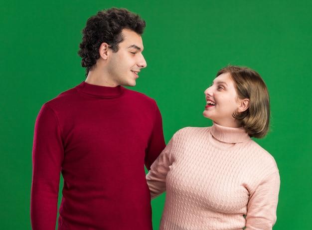 Jeune couple le jour de la saint-valentin homme souriant femme joyeuse se regardant isolé sur mur vert