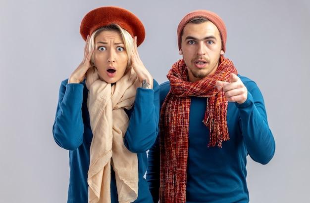 Jeune couple le jour de la saint-valentin portant un chapeau avec une écharpe fille effrayée a attrapé le gars de la tête vous montrant le geste isolé sur fond blanc