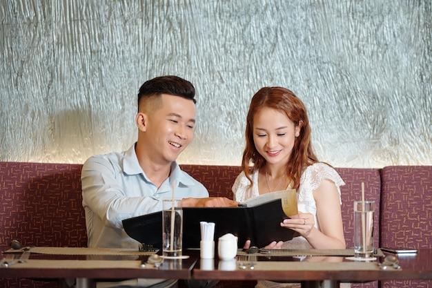 Jeune couple joyeux assis à la table du restaurant, lisant le menu et choisissant de la nourriture pour le dîner