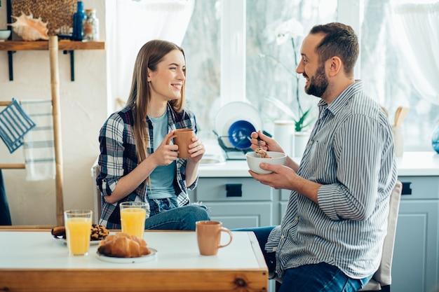 Jeune couple joyeux dans des vêtements décontractés souriant et prenant son petit déjeuner à la maison
