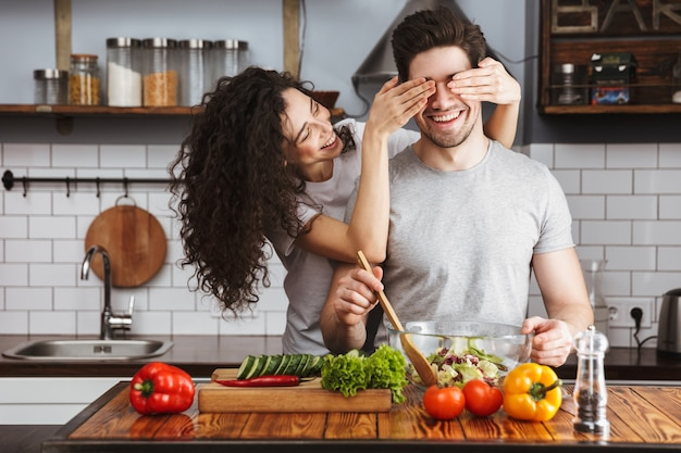 Jeune couple joyeux et excité cuisinant une salade saine assis à la cuisine, la femme couvre les yeux des hommes