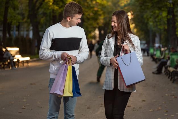 Un jeune couple joyeux marche après le shopping et tient des sacs colorés.