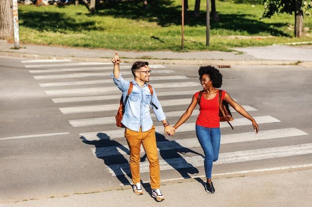 Jeune couple joyeux qui court dans la rue et souriant.