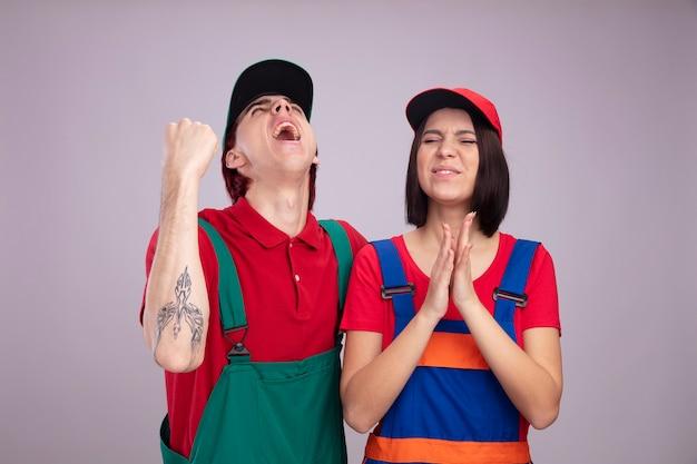 Jeune couple joyeux en uniforme de travailleur de la construction et cap guy levant faisant un geste oui fille applaudissant les yeux fermés