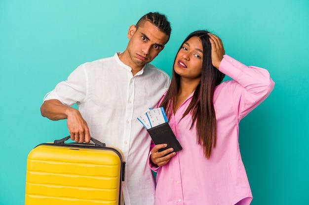 Jeune couple latin allant voyager isolé sur fond bleu étant choqué, elle s'est souvenue d'une réunion importante.