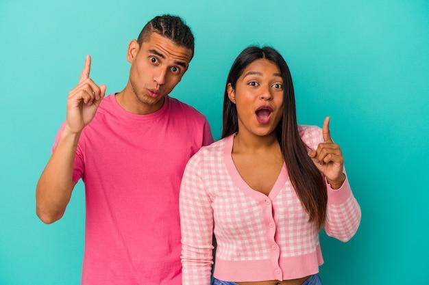 Jeune couple latin isolé sur fond bleu ayant une idée, concept d'inspiration.