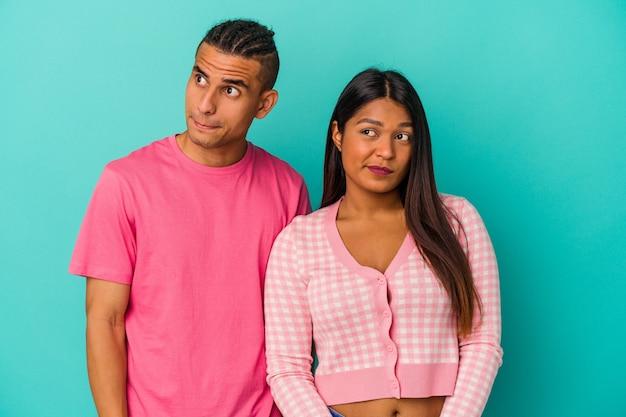 Jeune couple latin isolé sur fond bleu confus, se sent dubitatif et incertain.
