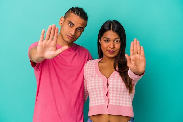 Jeune couple latin isolé sur fond bleu debout avec la main tendue montrant un panneau d'arrêt, vous empêchant.