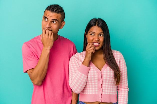 Jeune couple latin isolé sur fond bleu détendu en pensant à quelque chose en regardant un espace de copie.
