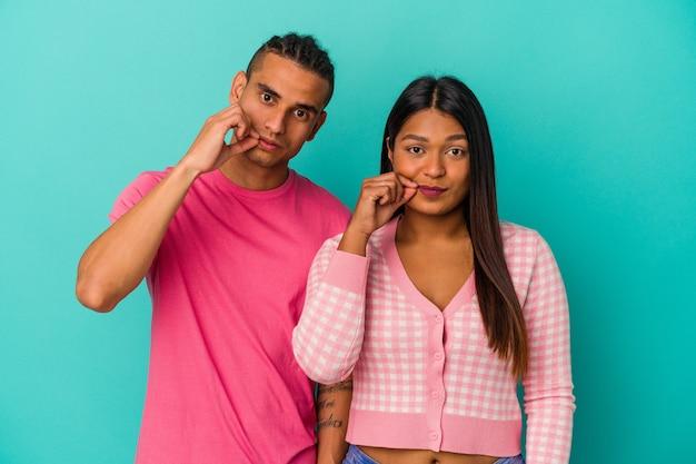 Jeune couple latin isolé sur fond bleu avec les doigts sur les lèvres gardant un secret.