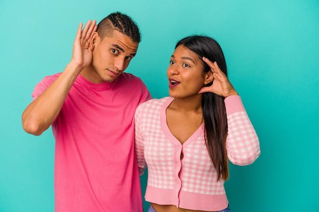Jeune couple latin isolé sur fond bleu essayant d'écouter un potin.