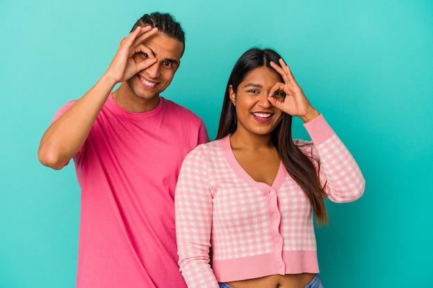 Jeune couple latin isolé sur fond bleu excité en gardant le geste ok sur les yeux.