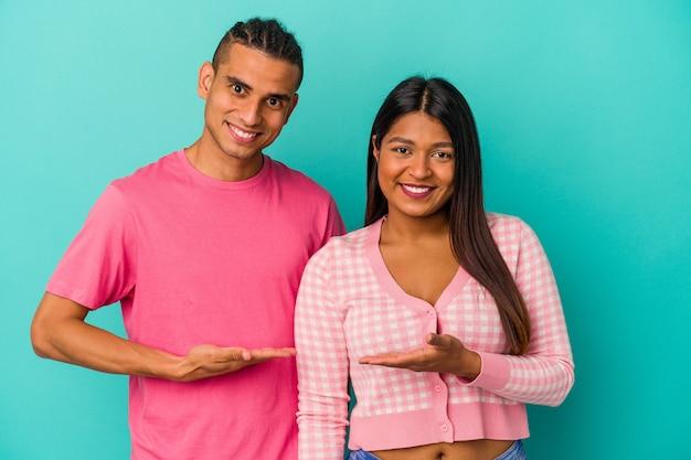 Jeune couple latin isolé sur fond bleu montrant un espace de copie sur une paume et tenant une autre main sur la taille.