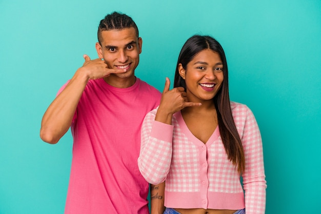Jeune couple latin isolé sur fond bleu montrant un geste d'appel de téléphone portable avec les doigts.