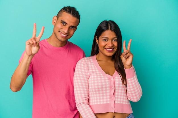 Jeune couple latin isolé sur fond bleu montrant le numéro deux avec les doigts.
