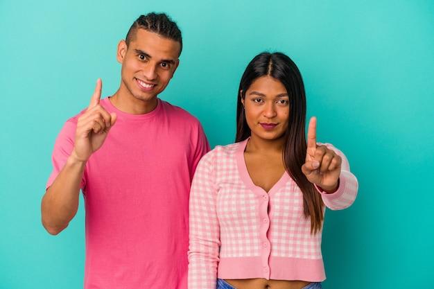 Jeune couple latin isolé sur fond bleu montrant le numéro un avec le doigt.