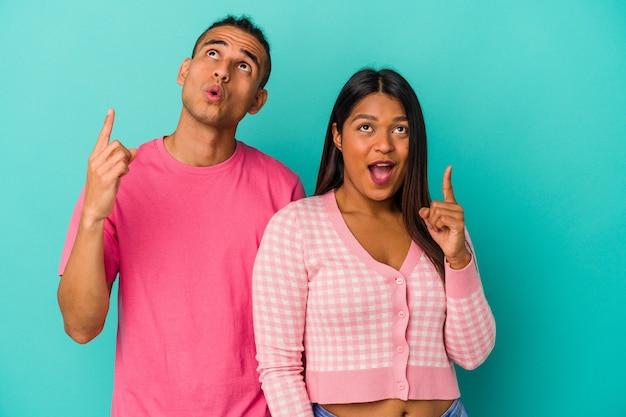 Jeune couple latin isolé sur fond bleu pointant vers le haut avec la bouche ouverte.