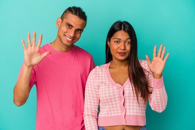 Jeune couple latin isolé sur fond bleu souriant joyeux montrant le numéro cinq avec les doigts.