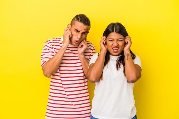 Jeune couple latin isolé sur fond jaune couvrant les oreilles avec les mains.