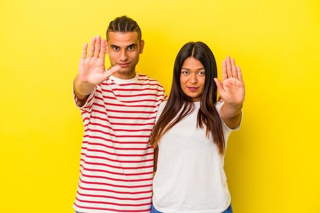 Jeune couple latin isolé sur fond jaune debout avec la main tendue montrant un panneau d'arrêt, vous empêchant.