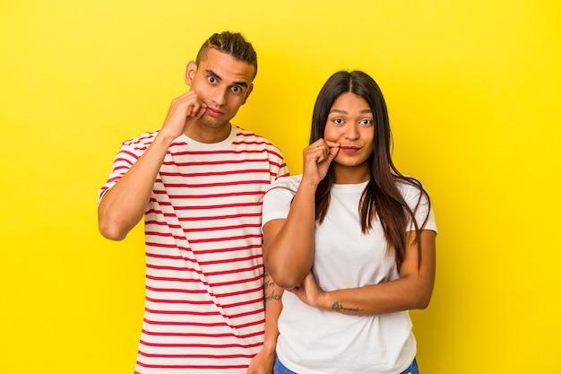 Jeune couple latin isolé sur fond jaune avec les doigts sur les lèvres gardant un secret.