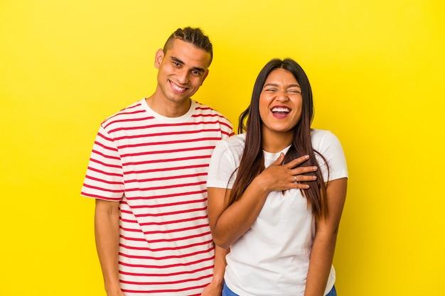Jeune couple latin isolé sur fond jaune éclate de rire en gardant la main sur la poitrine.