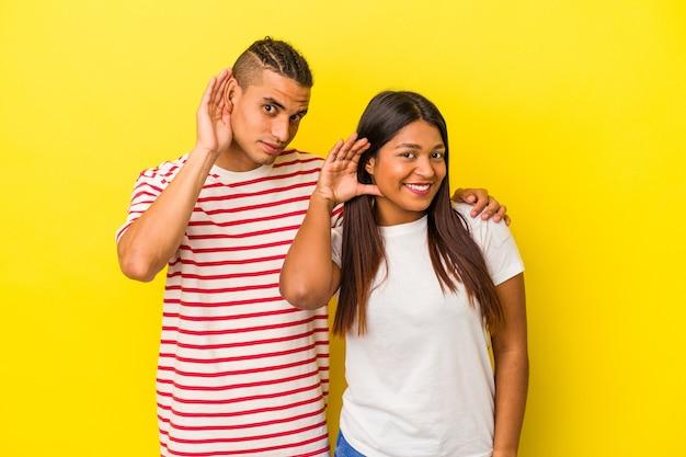 Jeune couple latin isolé sur fond jaune essayant d'écouter un potin.